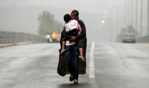 A Syrian refugee kisses his daughter as he walks through a rainstorm towards Greece's border with Macedonia, near the Greek village of Idomeni, September 10, 2015. Most of the people flooding into Europe are refugees fleeing violence and persecution in their home countries who have a legal right to seek asylum, the United Nations said on Tuesday. REUTERS/Yannis Behrakis - RTSFW6